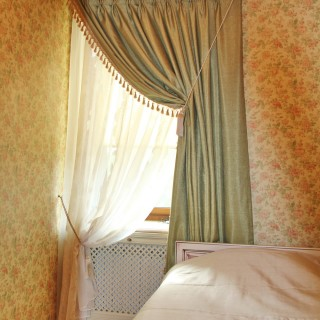 Классическая штора из ткани блекаут, с бахромой, в небольшую но очень уютную спальню.